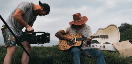 Image of man recording video of guitarist